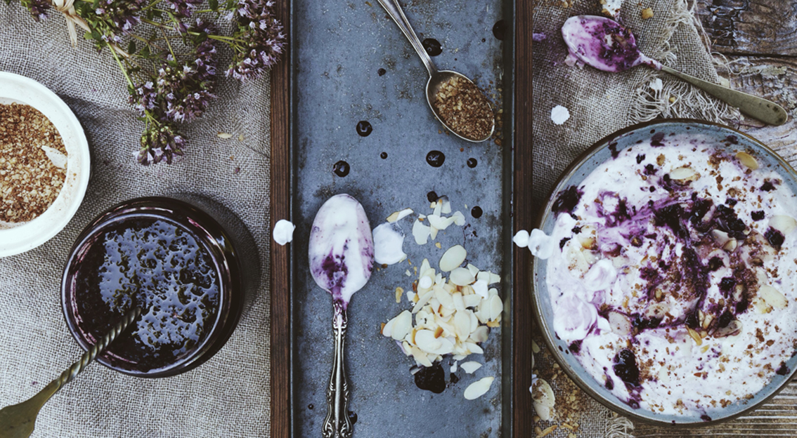 natural fresh white yogurt with blackberries jam, muesli and almond slices on bowl