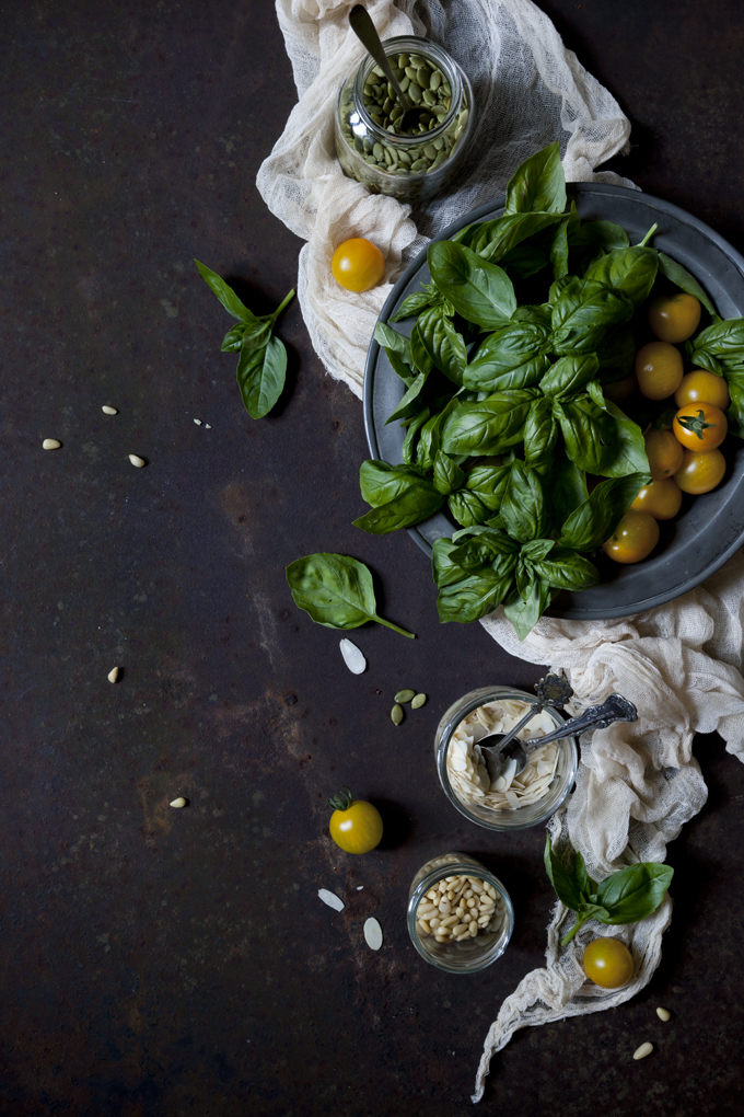 fresh basil leafs and yellow cherry tomatoes on rusty surface with seeds on jars