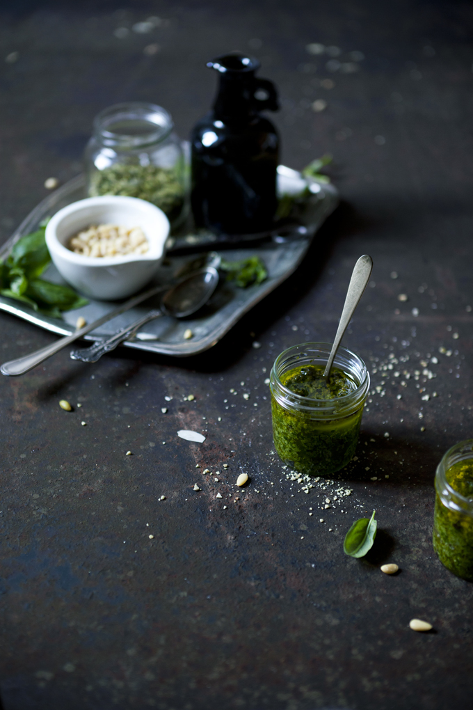 homemade preparation of pesto with pine nuts and fresh basil on a rusty table