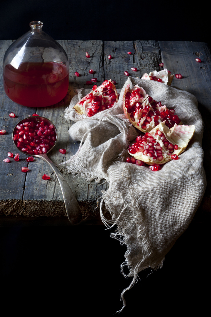 pieces of pomegranate and grains on spoon on rustic cloth with pomegranate juice on vintage glass bottle