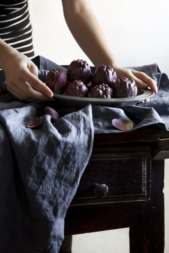 woman hands holding tray full of raw purple artichokes on rustic table with blue drape