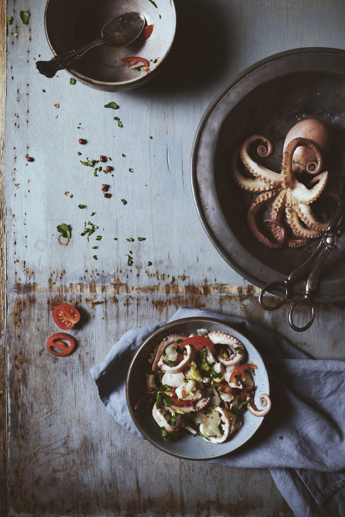 cooked small octopus on plate on blue rustic background with fish and vegetables salad on bowl