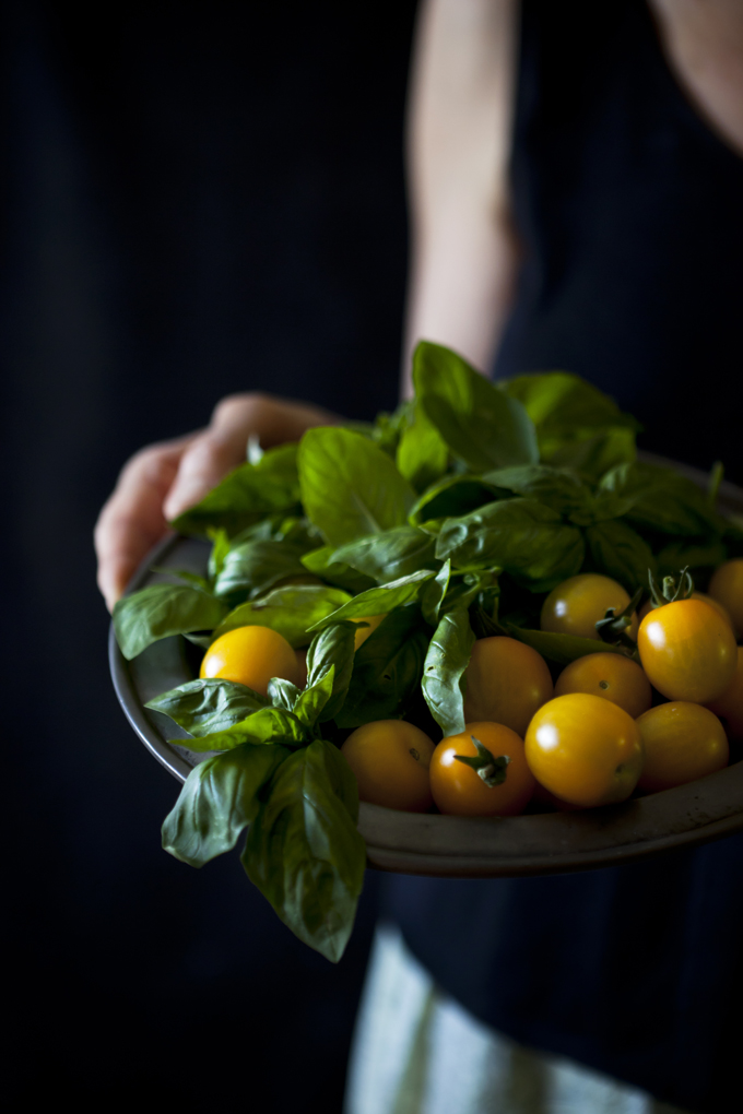 person holding a plate with fresh basil leafs and yellow cherry tomatoes