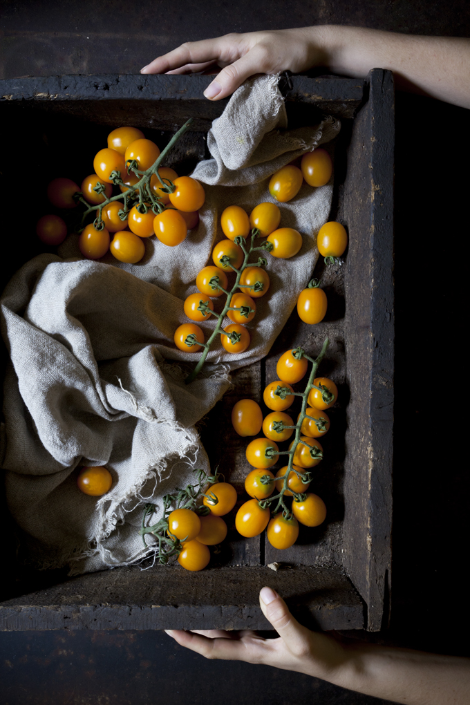 person holding bunch of yellow cherry tomatoes on a old wooden box