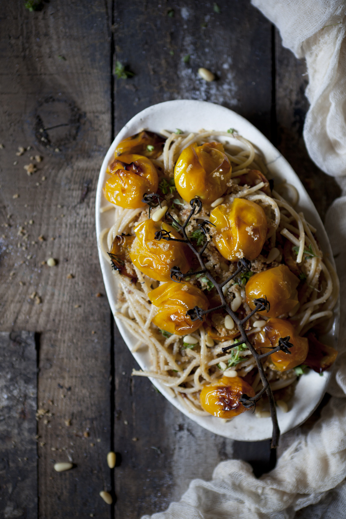 spaghetti with roasted yellow cherry tomatoes and pine nuts served on a oval-shape plate