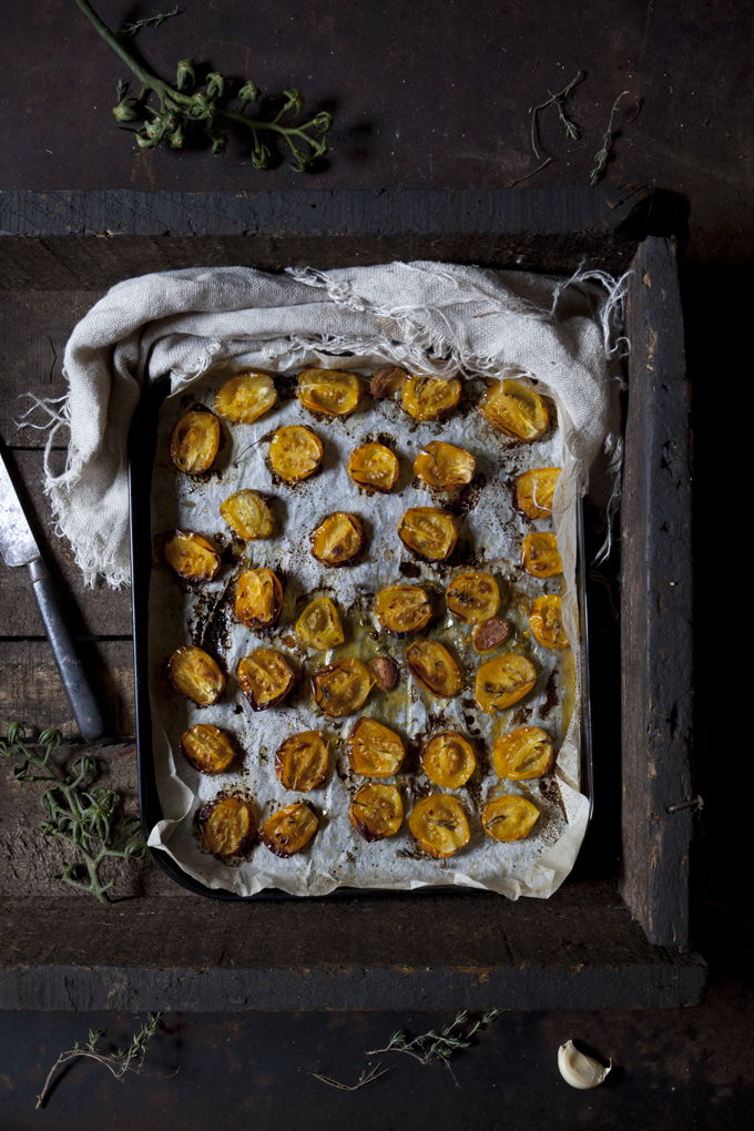 Overhead view of a baking tray of oven-roasted yellow tomatoes on a rustic wooden box